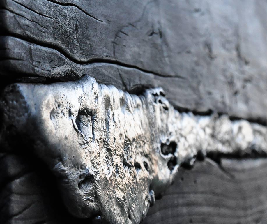 particolare lampada da parete in legno e alluminio di recupero